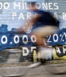 """A man rides his bicycle past graffiti painted on a wall in Burgos, central Spain, June 28, 2012. The graffiti reads in Spanish: """"50,000 million for rescuing banks and five million unemployed""""."""