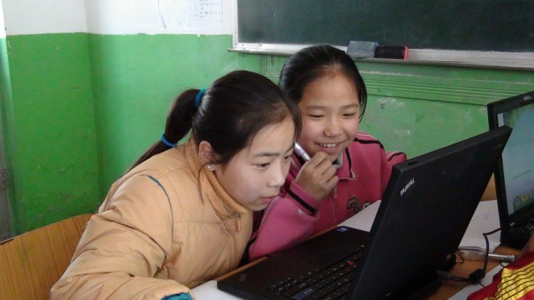 Two female Chinese students looking at a laptop in a classroom with chipped paint on the walls.