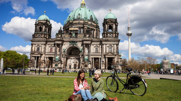 Two students sitting on grass in front of church in Berlin