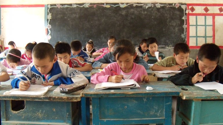 Middle school kids work at desks in a run down classroom in rural China.