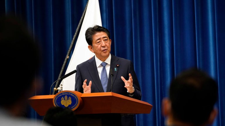 Japanese Prime Minister Shinzo Abe speaks at a podium with audience seen at the front