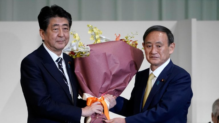 Japan's outing Prime Minister Shinzo Abe and incoming Prime Minister Yoshihide Suga hold a flower bouquet