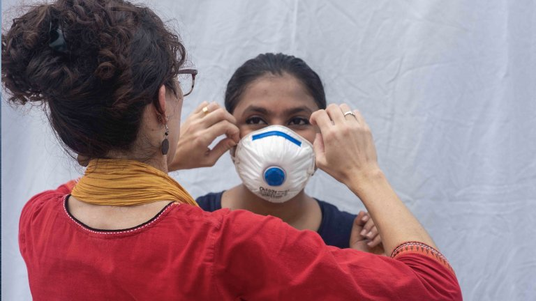 Ashley Styczynski shows a colleague in Bangladesh how to wear an N95 mask to protect her against COVID-19.