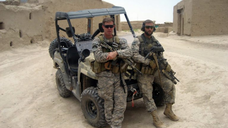 Two soldiers in front of car