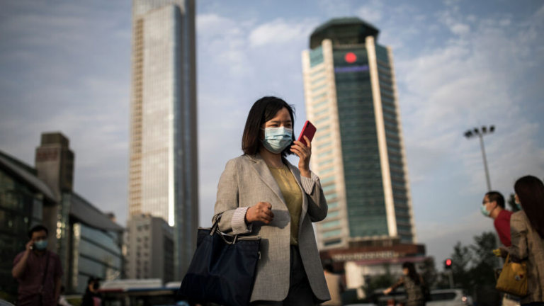 A professional looks at their phone while wearing a mask in a busy downtown area.