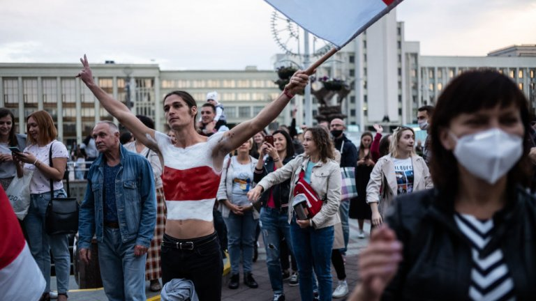 man waiving flag at protest in Belarus