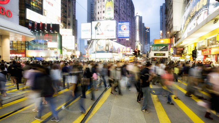 A busy crosswalk in a city with many people crossing the street in China.