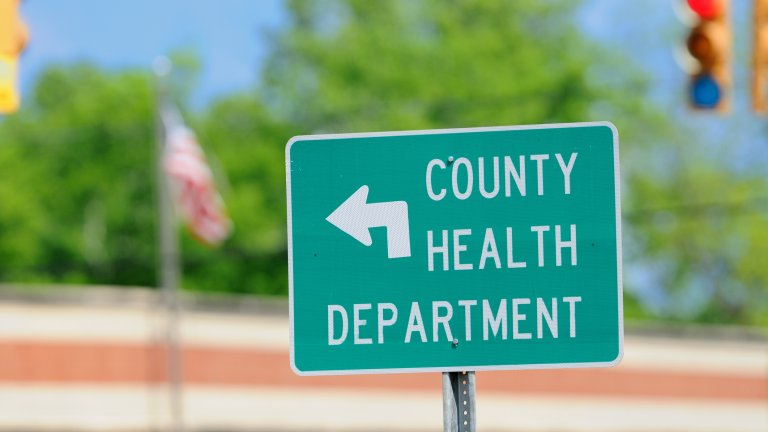 A traffic sign pointing to the county health department.