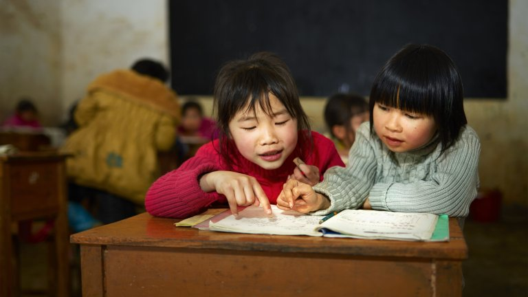 Chinese school children sit at a desk in a rural village school classroom.