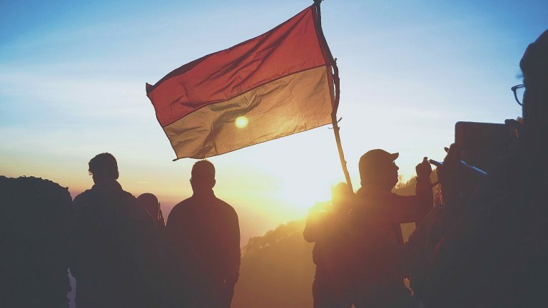 Silhouettes carrying a flag of Indonesia with a sunset or sunrise in the background