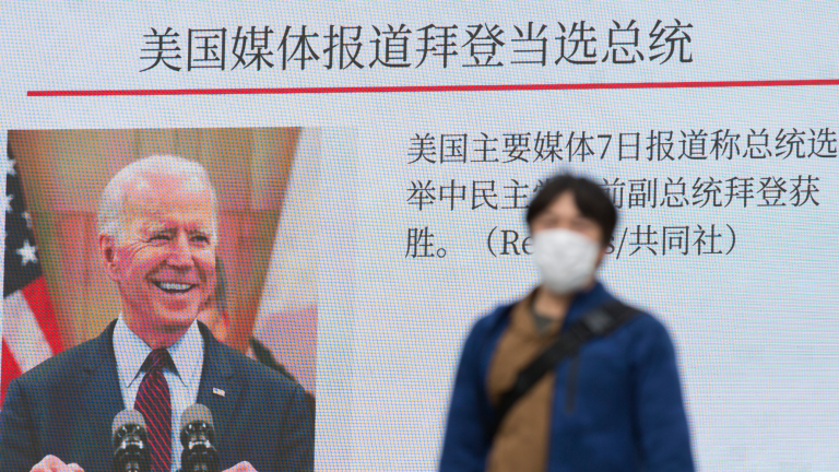 A man walks past a digital screen showing images of President-elect Joe Biden in a news program.