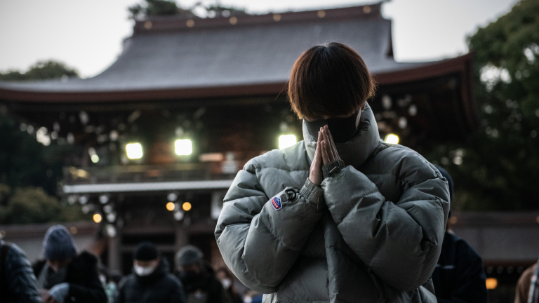 A man wearing a face mask prays for the new year at Meiji Shrine in Tokyo, Japan.