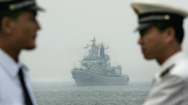 A naval ship in the South China Sea in the background fo two officers.