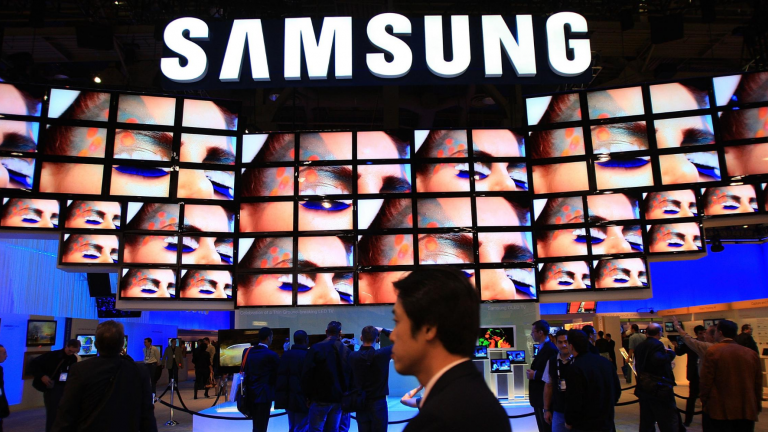 Show attendees watch a flat-screen television display at the Samsung booth during a convention