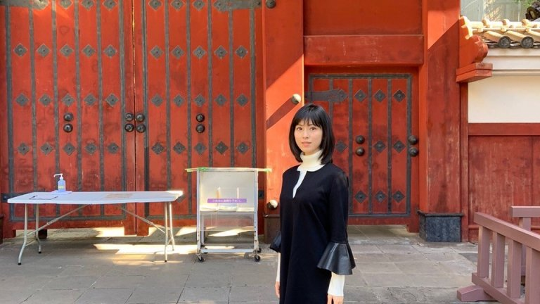 female student standing in front of Akamon in Japan