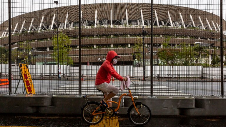 A man cycles past a security fence outside the New National Stadium, the main stadium for the Tokyo Olympics, on June 23, 2021 in Tokyo, Japan