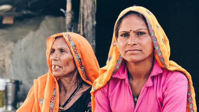 Two women sitting outdoor in Khidarpur Jadoo, Rajasthan, India.