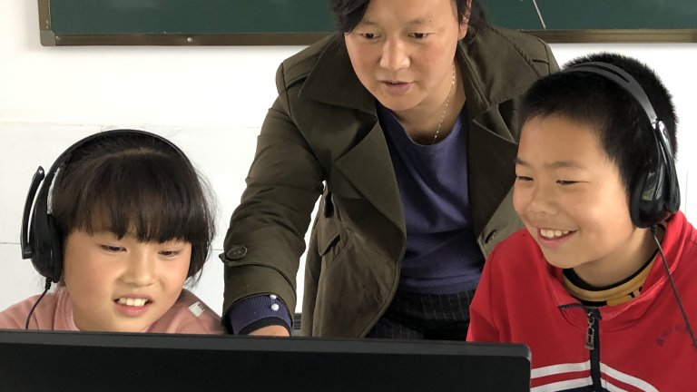 Two smiling Chinese students wearing headphones and looking at a computer screen with a teacher behind them gesturing to the screen.