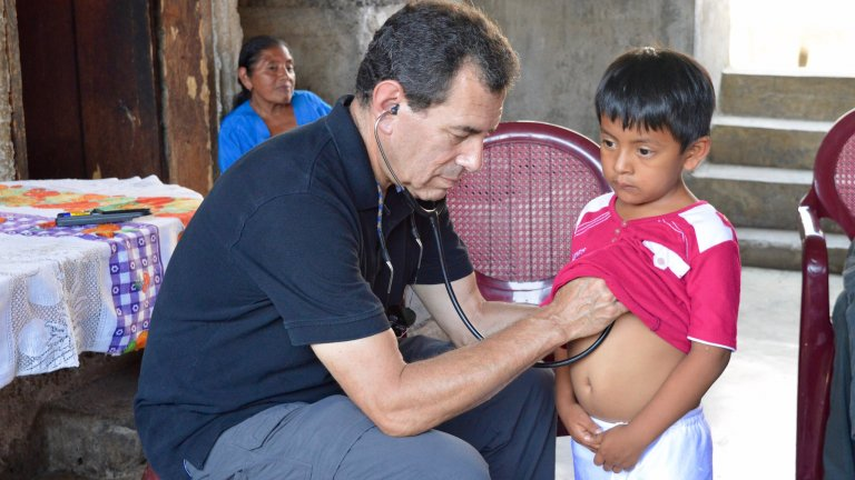 Stanford Health Policy's Paul Wise treats a boy in Guatemala.