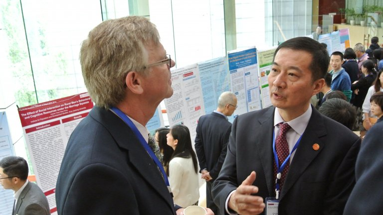 Closeup on two men speaking during a conference on demographic change and social development at Xi'an Jiaotong University, China, April 2016.