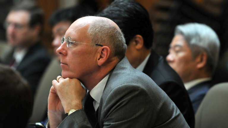 British diplomat John Everard seated at a Korea Program roundtable, listening to a discussion.
