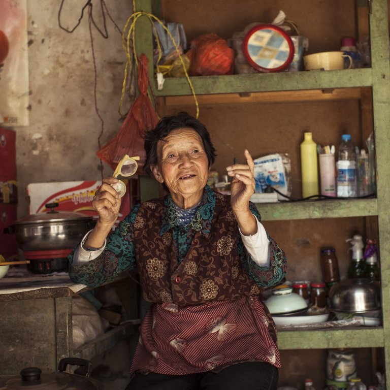 Older Tibetan woman sits in her living room in China.