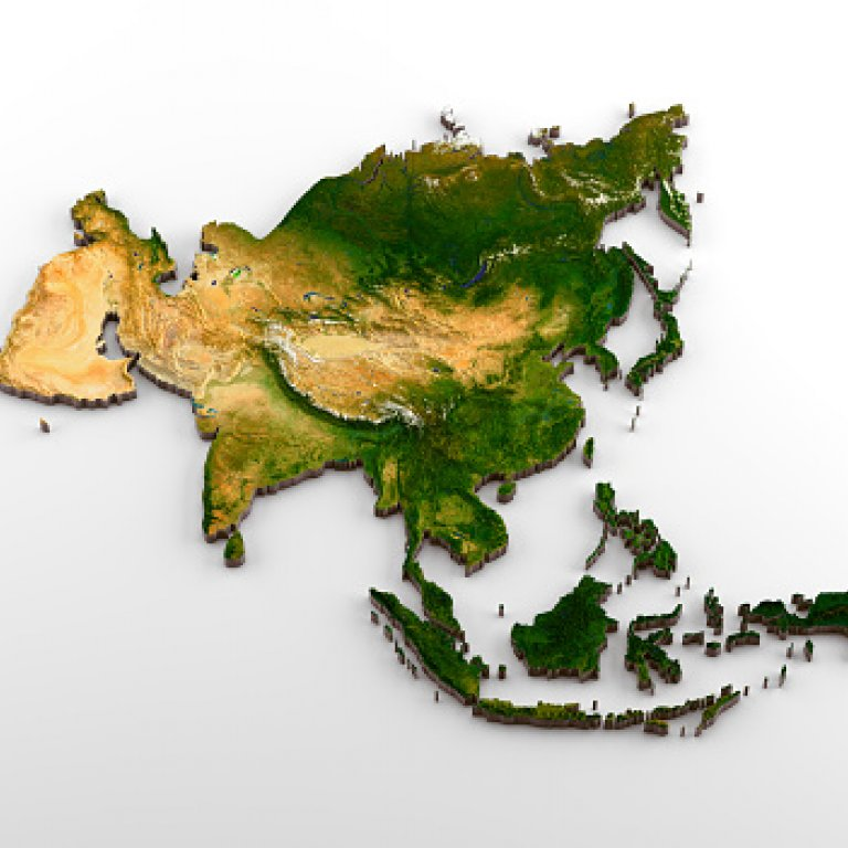 a magnifying glass focused on Asia on a map