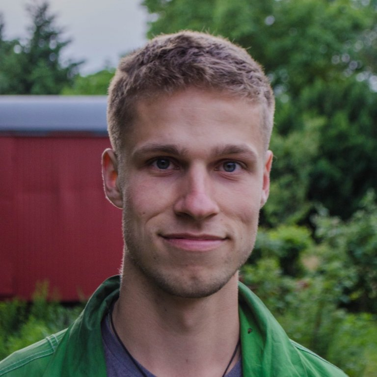 A headshot of Justin Braun. Justin is smiling slightly and standing outside.