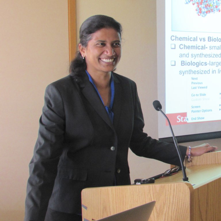A female Global Affiliate visiting fellow at a podium delivering a presentation in front of an audience.