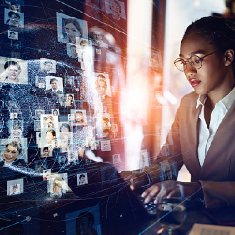 woman on computer in front of computer screen of faces