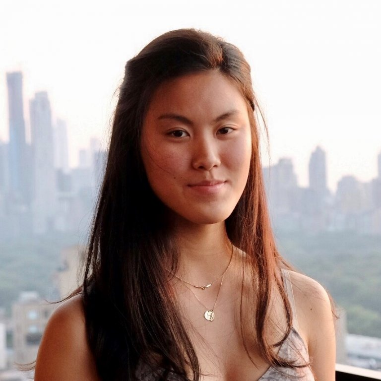 A headshot of Hanna Yip. Hanna is standing on a rooftop and has a faded skyline behind her.