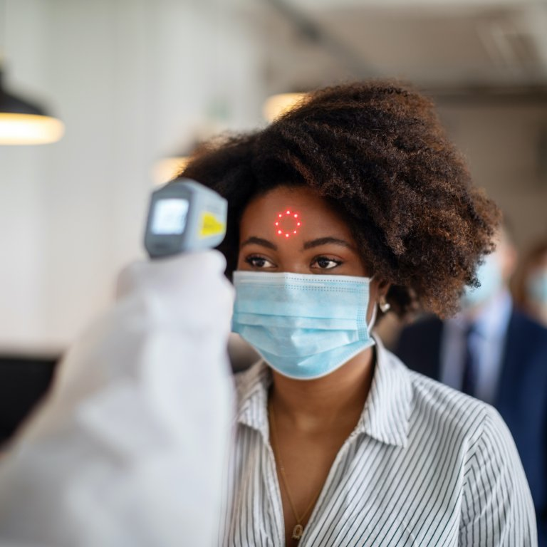 A Black woman wearing a mask gets her temperature taken.