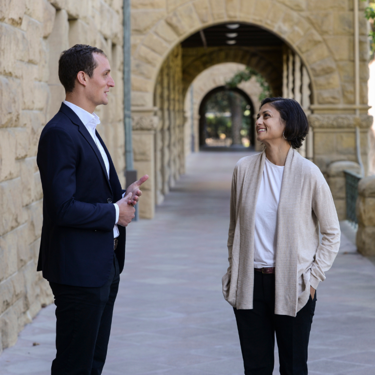 A man and a woman standing and talking at the entrance to Encina Hall, Stanford