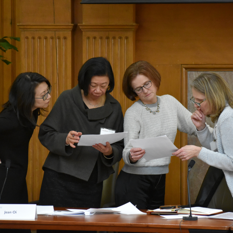 Four women standing and examining printed papers next to a conference room table with scattered paper on it
