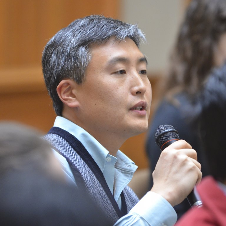 APARC faculty Yong Suk Lee speaks to a microphone among audience members during a Q&A session.