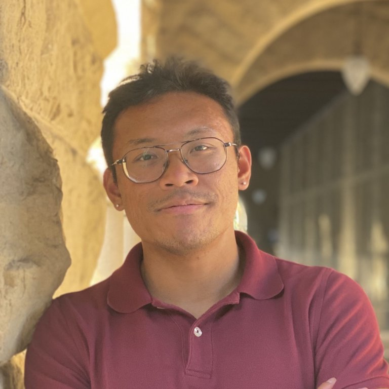 A headshot of Joseph Pagadora. Joseph is standing outside on the Stanford campus leaning against a pillar.