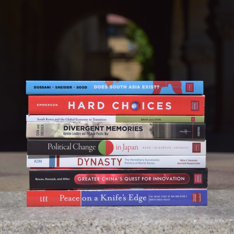 A collection of books published in Shorenstein APARC in-house monograph series set against the background of Encina Hall entranceway.