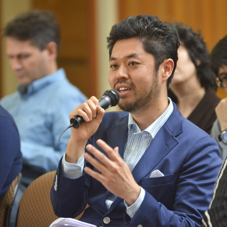 Global Affiliate Visiting Fellow speaks to a microphone while seated among an audience at an APARC event.