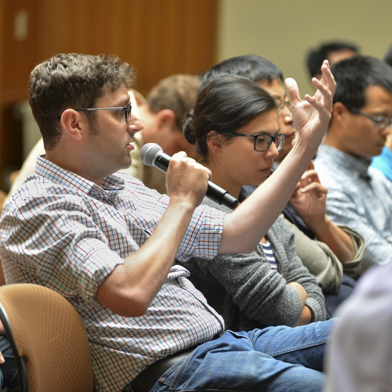 Event attendee seated in a lecture hall among other audience members, speaking to microphone.