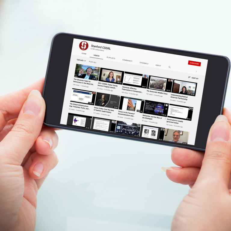 Woman holding phone with CDDRL YouTube page on screen