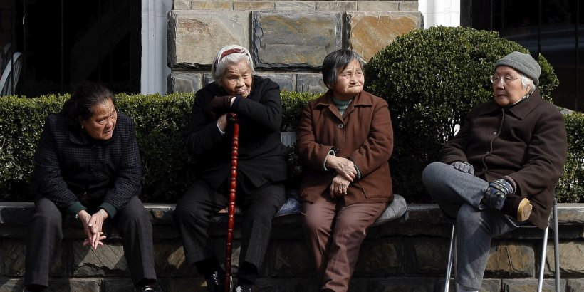 Four elderly Chinese people sitting outdoors.