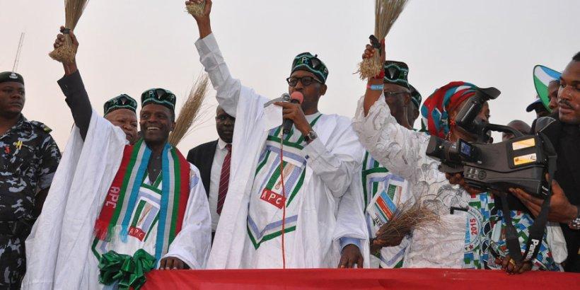 general buhari holding a broom at a campign rally