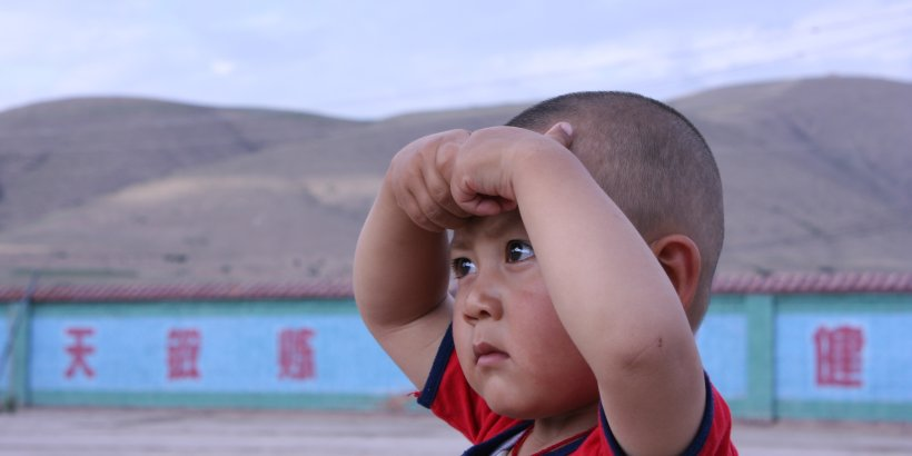 A young child with hands on forehead looking away from the camera into the distance standing in front of a wall with Chinese characters on it and distant mountains.