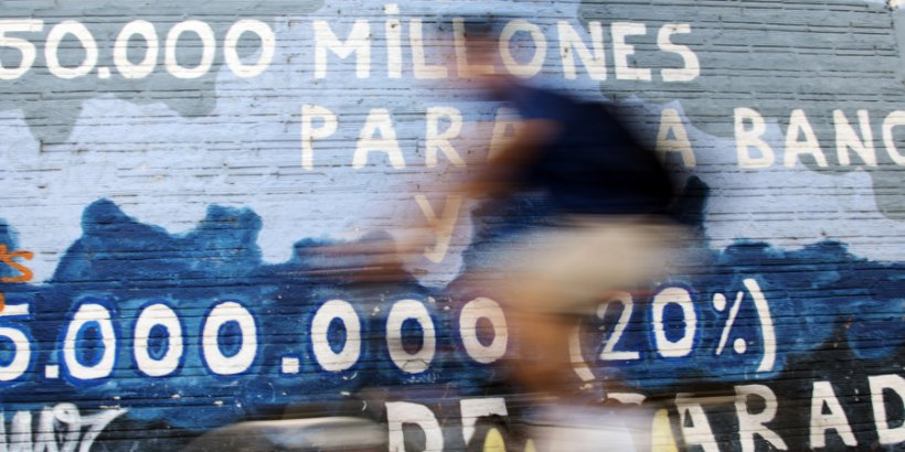 Image of a man riding his bicycle past graffiti about the Spanish bail out and unemployment painted on a wall in Burgos.