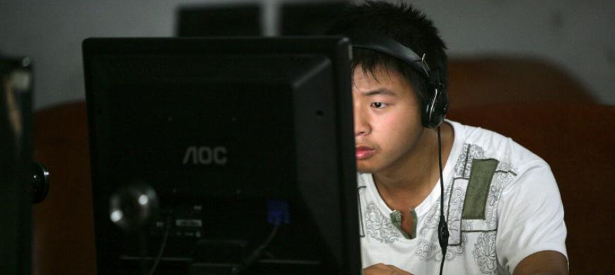 A man surfs the web in a netcafe in Youyang County of Chongqing Municipality, China