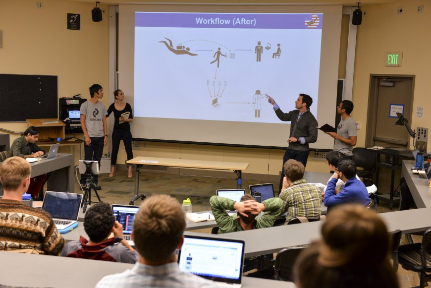 "A student team briefs the class on a wearable sensor they're developing for an elite unit of U.S. Navy SEALs – a product they're pitching as ""fitbit for America's divers."""