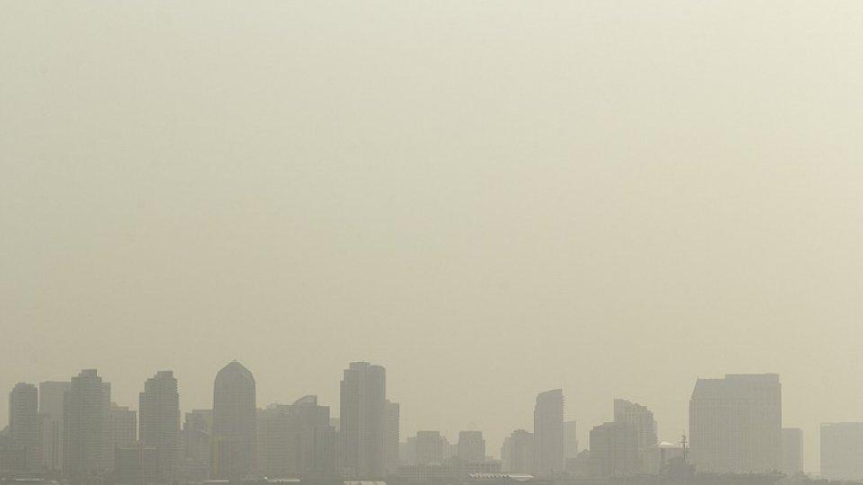 A city skyline under a smoky brown sky