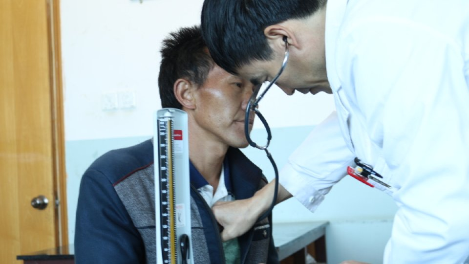 A doctor examines a patient using a stethoscope in a barren room in rural China.