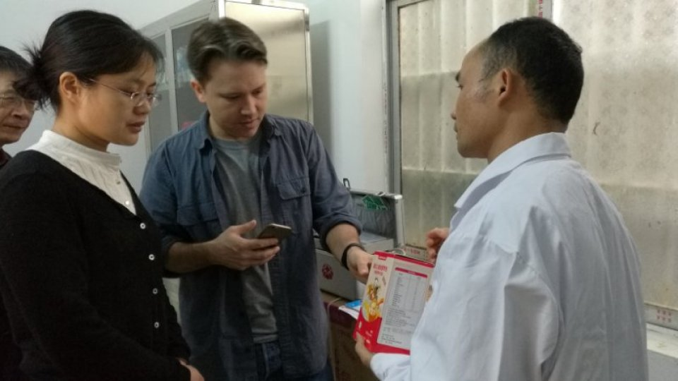 Two researchers talk to a doctor in a rural clinic in China.