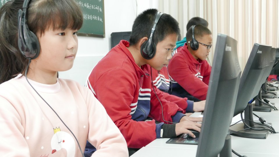 Three young students wearing headphones and working on desktop computers in a classroom.